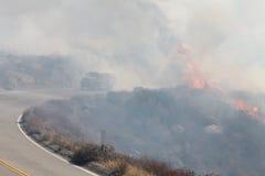 Silverbranden i Beaumont Kalifornien ~ 2013 ~ brandbränningen längs vägen med brandlastbilen som igenom kör Royaltyfri Foto