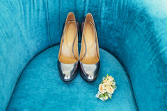 Silvering bride shoes with wedding boutonniere on blue couch Stock Photo