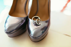 Silvering bride shoes with wedding rings Royalty Free Stock Photos