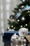 Silverjulbollar och blå giftbox Arkivbild