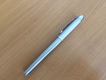 Silverpenna på det bruna skrivbordet Royaltyfri Fotografi