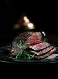 Silverside Roast Beef. Creatively lit, fresh British roast beef sliced for serving against a dark background with rosemary herb garnish. Generous accommodation Stock Photography