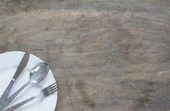 Silversked, gaffel och knive i platta på gammal, rostig träbaksida arkivfoton