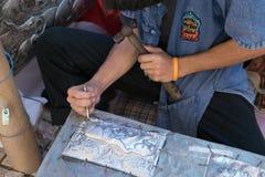Silversmedhantverkare som snider elefanten på en silverplatta (metall Fotografering för Bildbyråer
