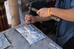 Silversmedhantverkare som snider elefanten på en silverplattametall Royaltyfri Fotografi