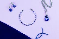 Silversmyckenuppsättning med den blåa safirstenen på pastellfärgad bakgrund Arkivfoton