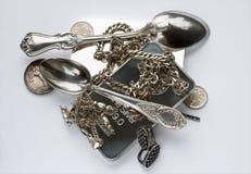 Silverstänger, gamla mynt, en tesked, en kaffesked, örhängen och kedjor Royaltyfri Bild