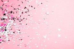 Silverstjärnor blänker på rosa pastellfärgad bakgrund royaltyfri fotografi