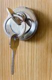 Silvertangenten sätts in in i nyckelhålet Närbild arkivfoton