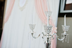 Silvertappningljuskrona mot bröllopbåge på ceremoni Fotografering för Bildbyråer