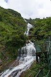 Silvervattenfall med den ärke- bron Arkivfoto