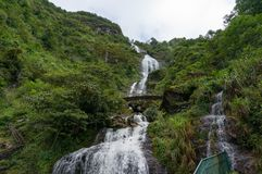 Silvervattenfall med den ärke- bron Royaltyfria Bilder