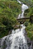 Silvervattenfall med den ärke- bron Arkivfoton