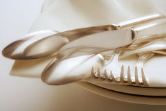 Silverware. Closeup of silverware on pile of plates with white cloth Stock Images