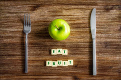 Silverware and apple on wooden table with sign Eat fruit Royalty Free Stock Photography