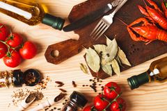 Silverware on the board with spices, cherry tomatoes and cancers. Set from silverware on the board, different spices, boiled cancers, cherry tomatoes and olive stock photography