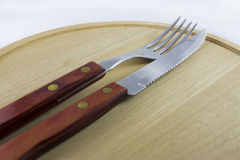 Silverware on Dish of Natural Wood. Fork and knife with red wooden handle on a plate of natural wood royalty free stock photography