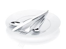 Silverware or flatware set of fork, spoons and knife over plates Royalty Free Stock Photos
