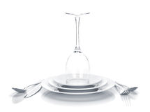 Silverware or flatware set and wine glass over plates Royalty Free Stock Images