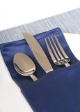 Silverware in a folded blue napkin on white plate Stock Image