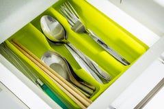 Silverware. In green tray, spoon, fork, chopsticks stock photo