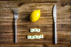 Silverware and lemon on wooden table with sign Eat fruit Royalty Free Stock Photos