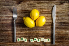 Silverware and lemons on wooden table with Bon apetit sign. Silverware and lemons on wooden vintage table with Bon apetit sign Stock Photo