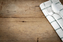 Silverware and napery on wooden background. Royalty Free Stock Photo