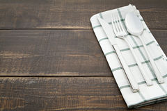 Silverware and napery on wooden background. Royalty Free Stock Images