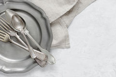 Silverware on a pewter plate. Various silverware on a pewter plate and gray flax napkin are on the background of gray concrete surface, with copy-space Royalty Free Stock Images