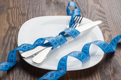 The silverware, plate and measuring tape, wooden background Stock Images