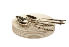 Silverware on plates. Silver spoon and fork on white plates Royalty Free Stock Photos