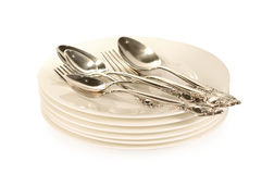 Silverware on plates. Silver spoon and fork on white plates Stock Images