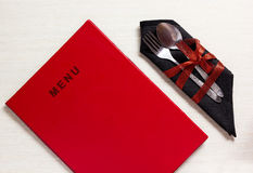 Silverware with red bow on black napkin next to menu Royalty Free Stock Images