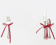 Silverware with Red Bows. Christmas, holiday silverware tied with red ribbon bows isolated on white background Royalty Free Stock Photography