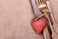 Silverware and red wooden heart. On gray cloth background Royalty Free Stock Photo