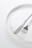 Silverware on a plate. Fork and knife silverware styled and on a round plate, white background Stock Image