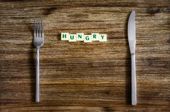 Silverware set on wooden table with sign Hungry Royalty Free Stock Images