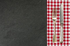 Silverware on a slate plate with a red checkered tablecloth Royalty Free Stock Photos