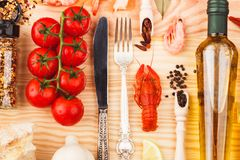 Silverware with spices, cherry tomatoes and cancers. Set from silverware, different spices, boiled cancers, cherry tomatoes, greenery and olive oil bottles on stock photo