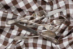 Silverware on a white and brown checked fabric Stock Images