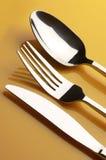 Silverware on yellow Royalty Free Stock Photos