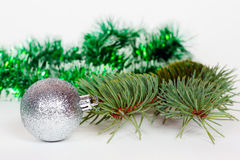 Silvery ball, pine branch and green tinsel Stock Images
