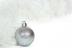 Silvery ball and white Christmas tinsel Stock Image