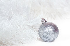 Silvery ball and white Christmas tinsel Stock Images