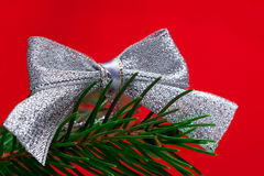 Silvery bow at red backdrop Royalty Free Stock Image
