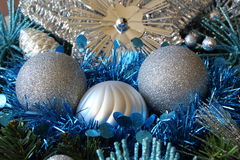 Silvery Christmas balls and blue tinsel on a Christmas wreath Stock Photos