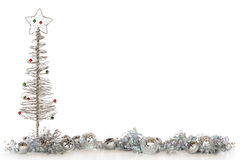 Silvery Christmas Border. A border composed of a wire Christmas tree, bells, shimmery bulbs and curly ribbon, all in sliver.   Isolated on white with plenty of Royalty Free Stock Image