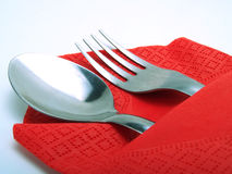 Silvery cutleries. A nice place with a silvery spoon and fork, covered by a nice red napkin royalty free stock image