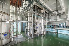 Silvery distillation columns entangled in a multitude of pipes, valves and sensors. Manufacture of alcohol Stock Image